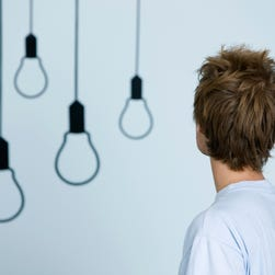 Young man looking at light bulb graphics on wall, rear view