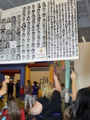 Parents and children look for their faces in the collage