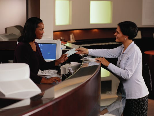Woman Handing the Teller a Check at a Bank