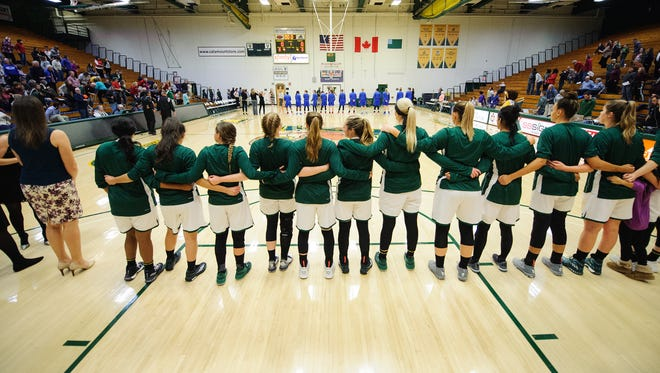 The teams listen to the national anthem during the women's basketball game between the American Eagles and the Vermont Catamounts in the first game of the TD Bank Classic at Patrick Gym on Friday.