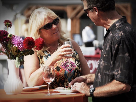 Cyndi Smith and Dan Von Trapp enjoy a glass of Willamette Valley Vineyards wine that was paired with their crab cakes from Bentley's Grill during the Pairings! event at the Oregon State Fairgrounds on Aug. 15.