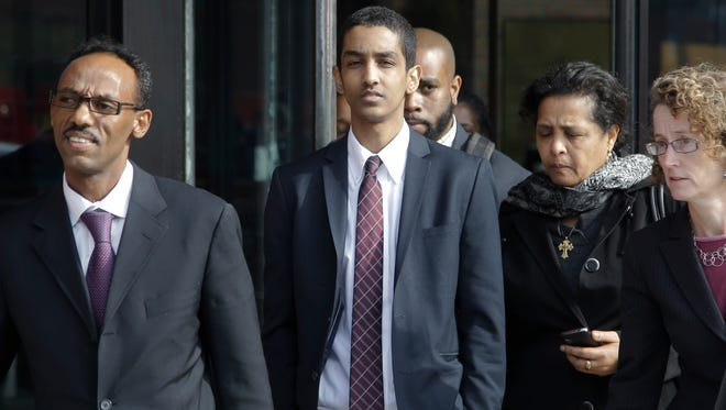 Robel Phillipos departs federal court with defense attorneys after he was convicted in Boston on Tuesday, Oct. 28, 2014.