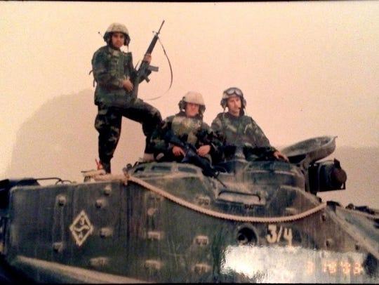 Sgt. Joel Ruiz (standing), then LCpl. Daniel Dineen