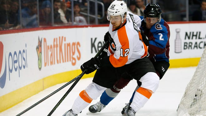Flyers left winger Michael Raffl picks up the puck as Colorado Avalanche defenseman Nick Holden defends.