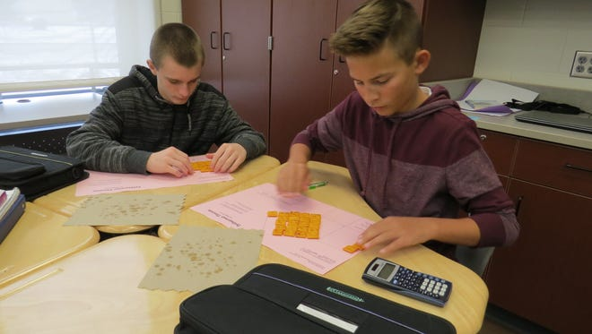 Port Clinton Middle School students Darick Hoyt, left, and Garrett Arnold use cheese crackers to solve an algebra problem.
