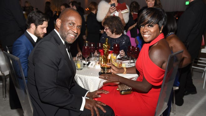 Viola Davis and her husband Julius Tennon grab a seat at the Governors Ball after the Oscars.