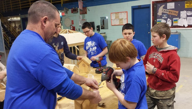 Dan Moscioni, Vanguard Tech Center construction trades teacher, assists Clyde Green Springs student Ridley Sabo in building a bird house during the Vanguard Tech Center's winter camp.