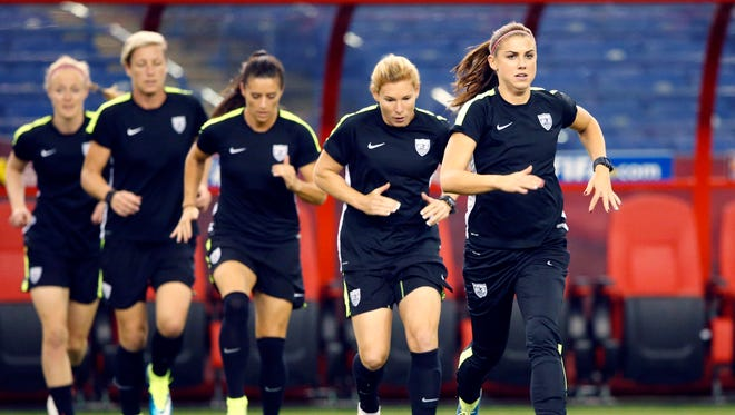 Alex Morgan leads her teammates in a drill.