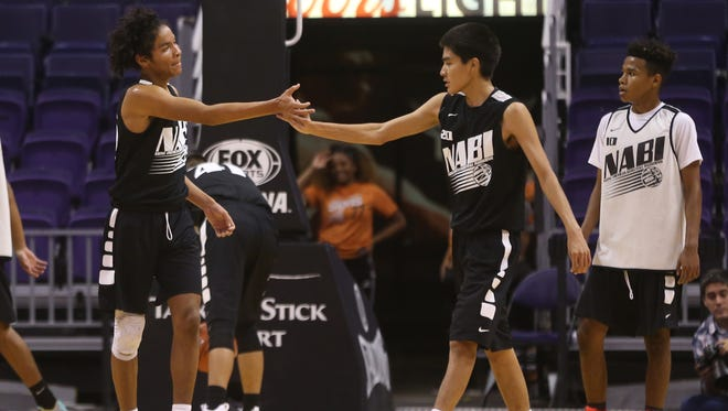 Barrow's Tahja Mayberry (L) high-fives Lionel Nez (20) during the Boys Silver Championship game at Talking Stick Resort Arena in Phoenix, Ariz. on July 15, 2017.