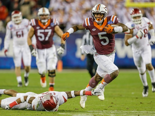 FILE - In this Dec. 29, 2016, file photo, Virginia Tech's Cam Phillips (5) dodges Arkansas' Santos Ramirez (9) during the second half of the Belk Bowl NCAA college football game in Charlotte, N.C. Phillips finished second on the team with 76 catches for 983 yards and five touchdowns last season, and could break all the school records Isaiah Ford set with another huge year. (AP Photo/Bob Leverone, File)