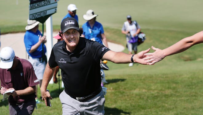 Phil Mickelson gets a high-five after a birdie on the ninth hole during the final round of the FedEx St. Jude Classic on Sunday.