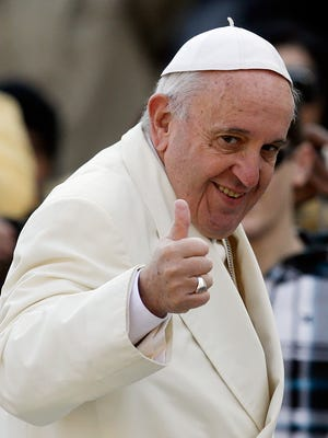 Pope Francis gives the thumbs up sign as he arrives on his the popemobile in St. Peter's Square for the weekly general audience, at the Vatican, Dec. 9.