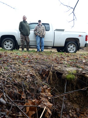 Gerald Parish and Charles Wooley stand at ground level of a minor sinkhole in Madison County about a mile from the area where Noah Chamberlin went missing on Jan. 14. Rescue workers are searching sinkholes much larger to try to find 2-year-old Noah.