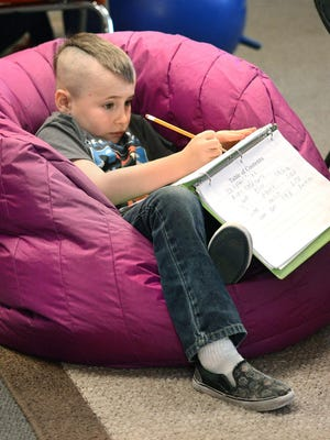 Tray-Sin Bies sinks into a comfortable beanbag chair to plow through the day's work at Orchards Elementary School in Lewiston, Idaho.