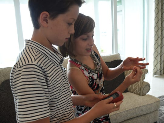 Lucas Lye, 12, helps his sister check her blood sugar