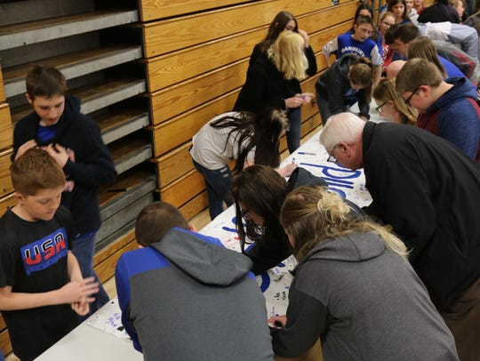 "Danbury students and staff sign a poster with ""#DHSSolidarity"""