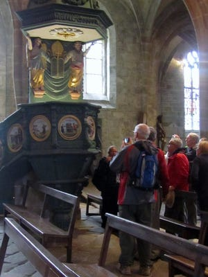 Visitors listen to talk about the 1707 pulpit depicting the story of Saint Ronan.