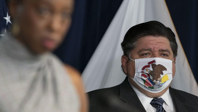 Illinois Gov. JB Pritzker listens to Dr. Ngozi Ezike, of the Illinois Department of Public Health, during a news conference at the Thompson Center in Chicago on Oct. 14, 2020.