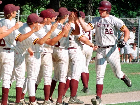 Mike Mueller is congratulated by teammates after hitting