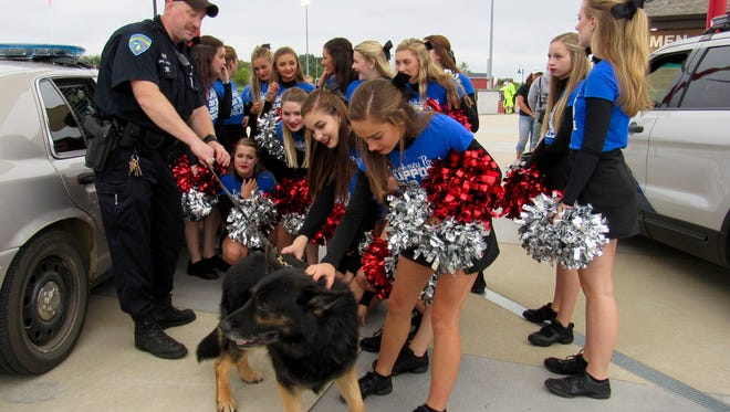 Pinckney K9 Police Officer Steven Hart and K9, Kizer, are greeted by the Pinckney Pom Team Friday.