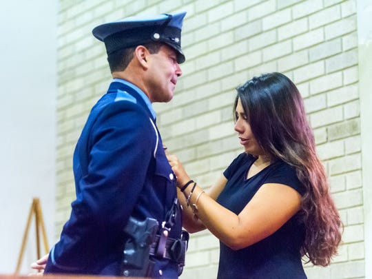 Officer Philip Martinez receives his pin from daughter