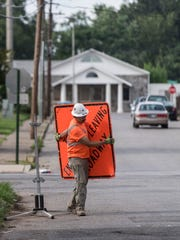 An Environmental Quality Management worker takes down a sign as the agency cleans up their workspace for the day at the intersection of Gum Street and S Evans Ave in Evansville, Ind., on Thursday, July 27, 2017. The Environmental Protection Agency estimates that it has removed lead and arsenic from around half of the contaminated residential properties that surround downtown Evansville, but still has about 2,000 properties remaining.