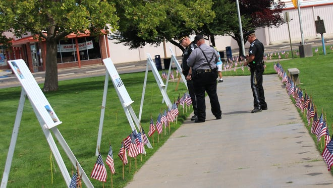 State Police officers, who were among those honored at the commemoraton read one of the lists of those who died on 9/11.  Gough Park was the site of the commemoration Sunday afternoon.