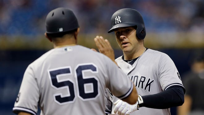 New York Yankees' Austin Romine, right, high fives first base coach Tony Pena after his RBI single off Tampa Bay Rays relief pitcher Enny Romero scored Chase Headley during the eighth inning of a baseball game, Saturday, May 28, 2016, in St. Petersburg, Fla. The Rays won 9-5.