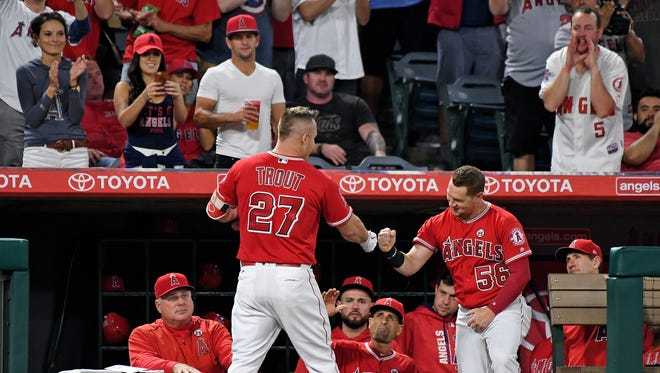 Los Angeles Angels center fielder Mike Trout (27) celebrates with right fielder Kole Calhoun (56) after hitting a solo home run in the first inning against the Seattle Mariners at Angel Stadium of Anaheim.