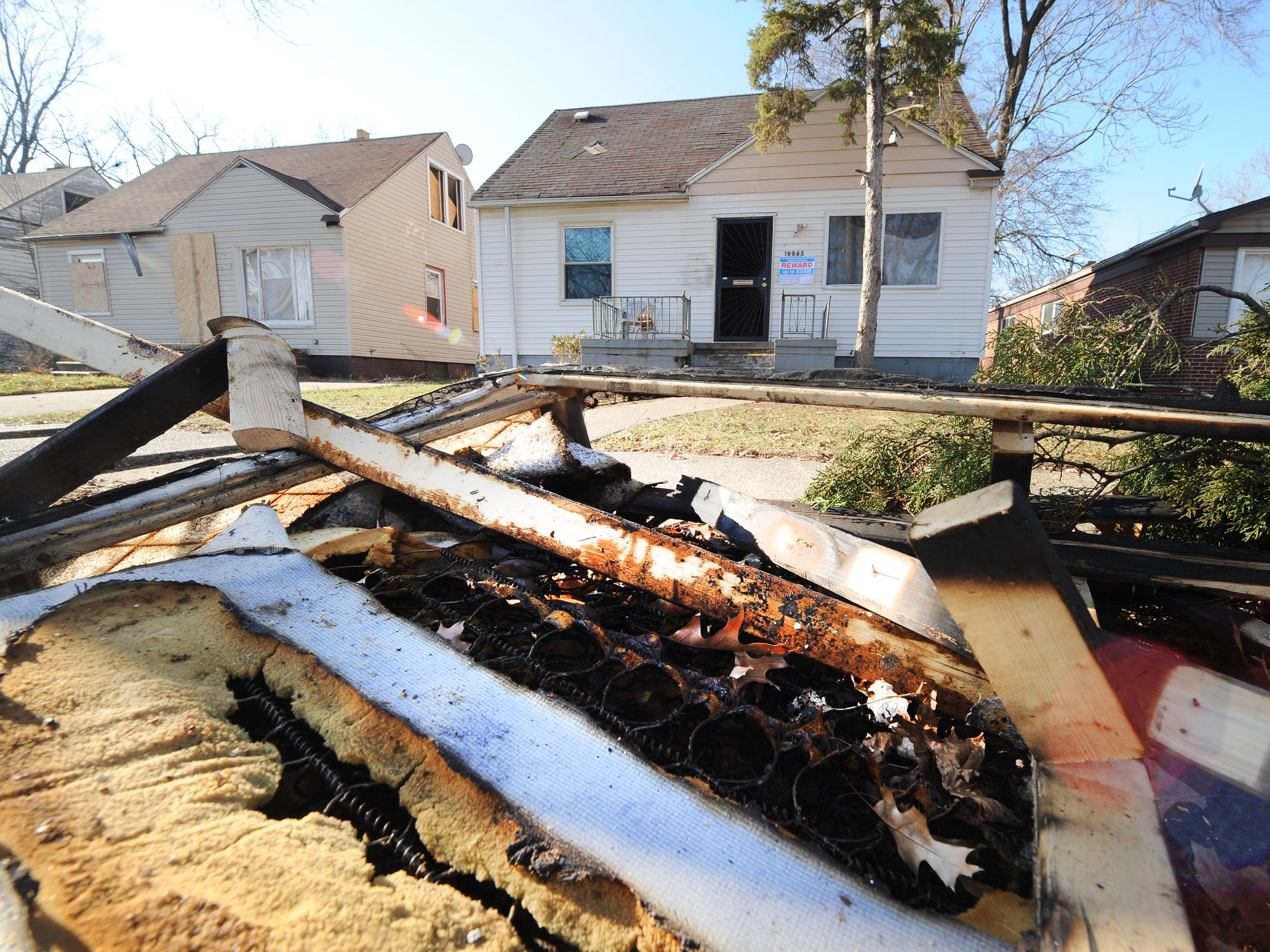 Charred items rest curb-side at the scene of a suspected