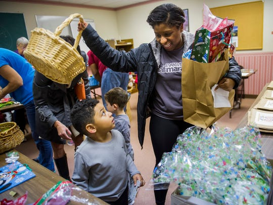 Donovan Quijada, 3, picks out gifts with his Aunt, Mychelle Christian, both of Evansville, during the Riley Angel Tree secret santa workshop at Christ Church in Evansville, Tuesday, Dec. 6, 2016.