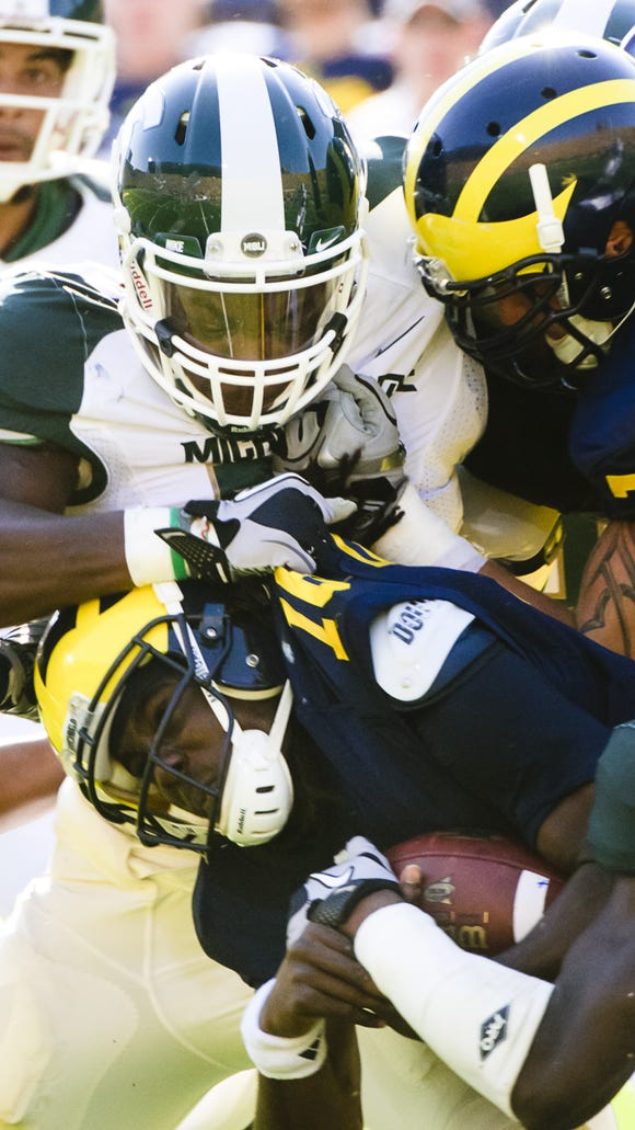 Greg Jones (top) of MSU fights off a block by Michigan's Taylor Lewan (77) to stop quarterback Denard Robinson (bottom) during their game during the Spartans' 2010 win in Ann Arbor.