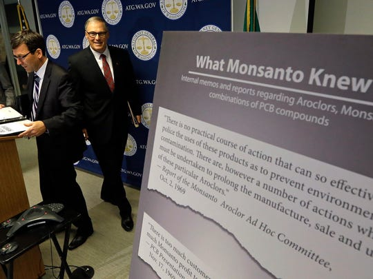 Washington Attorney General Bob Ferguson, left, and Gov. Jay Inslee head into a news conference where Ferguson announced a lawsuit against agrochemical giant Monsanto.