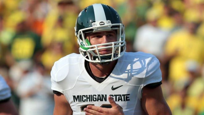 Michigan State Spartans quarterback Connor Cook (18) returns to the side line following a missed throw in the first half against the Oregon Ducks at Autzen Stadium.