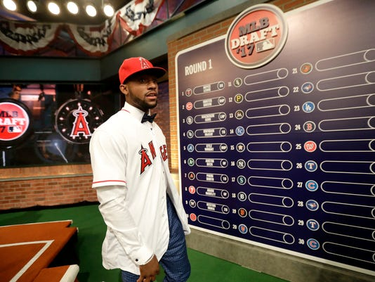 Jordon Adell, an outfielder and pitcher from Ballard High School in Louisville, Ky., walks off the stage after being selected No. 10 by the Los Angeles Angels in the first round of the Major League Baseball draft, Monday, June 12, 2017, in Secaucus, N.J. (AP Photo/Julio Cortez)