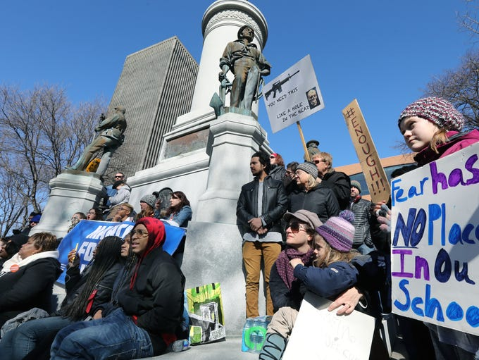 People surround a veterans monument as they protest