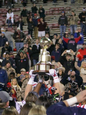 Ole Miss players present the Egg Bowl trophy to the fans following the Rebels' 31-28 victory over Mississippi State Thursday in Starkville.