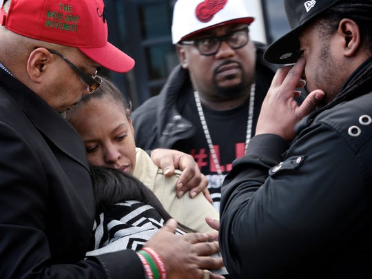 Minister Malik Shabazz, left, head of Marcus Garvey Movement/New Black Panther Nation, hugs the nieces of Janet Wilson, 31, who was shot and killed in January by Dearborn police, at a prayer service in February. Nieces are Cassie Bass and Talia Bass.