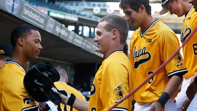 Iowa's Eric Toole, center, is greeted in the dugout following his solo home run off Michigan pitcher Ryan Nutof in the first inning of the NCAA Big Ten tournament college baseball game, Thursday, May 21, 2015, in Minneapolis.