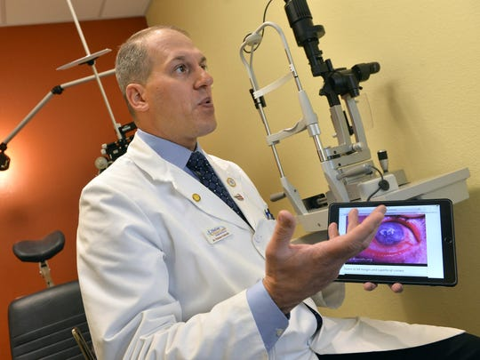 Optometrist Dr. Nicholas Colatrella holds a photo of an eye that's been severely injured by burns Wednesday at his offices at PineCone Vision Center in Sartell. Fireworks can be a real hazard, Colatrella says, because of the concussion damage, thermal burns and chemical burns that can cause severe injuries to the eyes. Wearing safety glasses and simply staying away from fireworks are two effective forms of prevention.