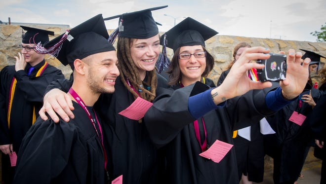 NMSU Bachelors of Science in Physics students Chas Hammond, left, Joni Clark and Khadijih Mitchell pose for a selfie before entering the Pan American Center for commencement ceremonies, May 14, 2016.