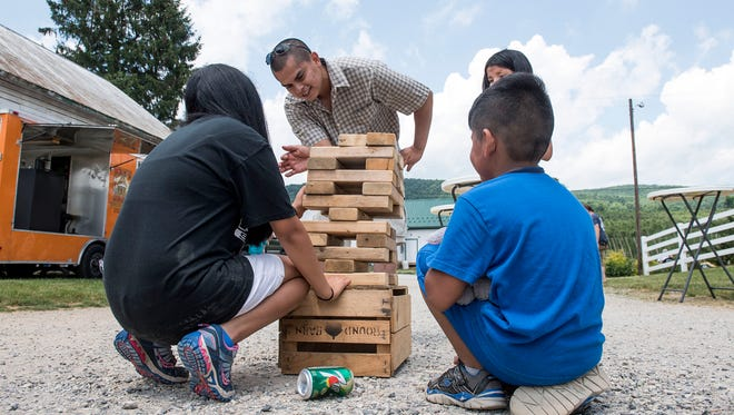 Lorenzo Moreno, center, plays Jenga with his three kids, Sunday, June 18, 2017. Moreno was struck by two vehicles a year and a half ago, and has made huge leaps in his recovery. Sunday, Historic Round Barn and Farm Market held a recovery celebration for Moreno, doubling as a Father's Day celebration.