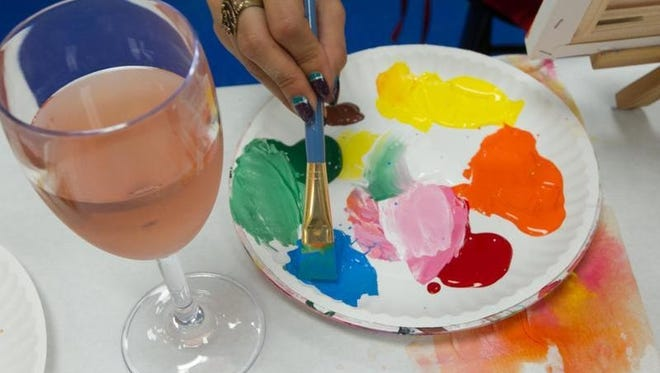 An artist dips her brush in paint with a glass of wine nearby at Yes You Canvas! in Oviedo.