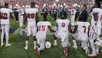 Nebraska linebacker Michael Rose-Ivey (15), defensive end DaiShon Neal (9) and linebacker Mohamed Barry (7) kneel during the national anthem.