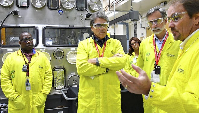 In this 2017 photo, U.S. Secretary of Energy Rick Perry, center, accompanied by Laboratory Director Charlie McMillan, second from right, learns about capabilities at the Los Alamos National Laboratory's Plutonium Facility from Jeff Yarbrough, right.