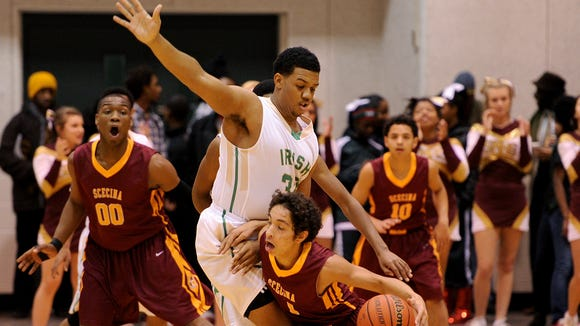 Scecina's Josh Rutland collides with Cathedral's Jared Thomas during the semifinals of the city basketball tournament, Saturday, January 25, 2014, in Indianapolis.