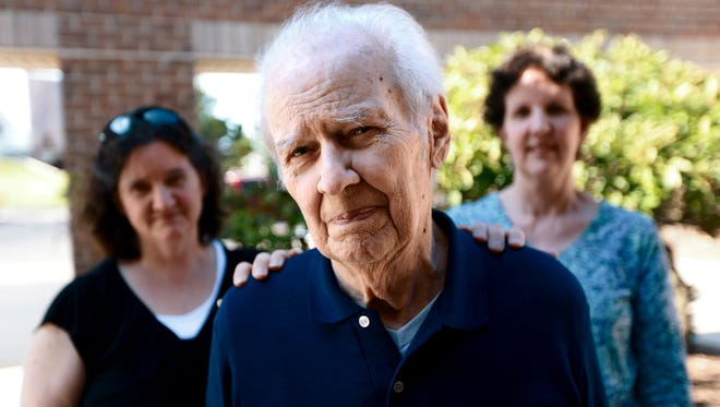 Frank Calcaterra, 87, stands with his two daughters, Cathy Schoenherr, 49, of North Carolina, left, and Charlotte Knutson, 58, of Minnesota, after discussing their case against Tangie Coleman, at the law offices of Karen Woodside in Livonia, Mich., on Thursday, July 17, 2014.