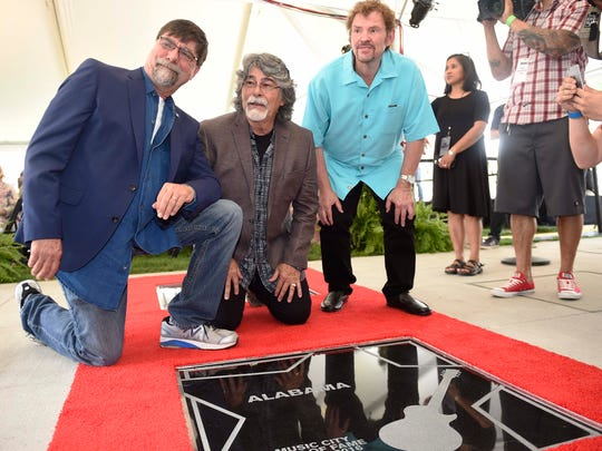 Alabama band members Teddy Gentry, Randy Owen and Jeff Cook pose during the Walk of Fame induction ceremony May 26, 2016, at Walk of Fame Park in Nashville.