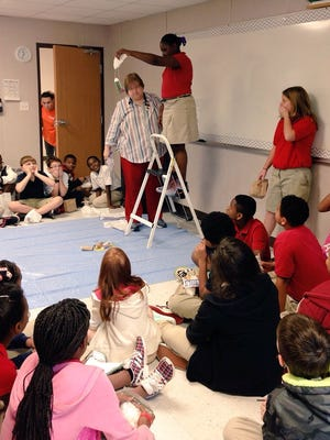 Cherokee Elementary fifth-graders await the drop of Precious Jefferson's container that she designed and built to protect a raw egg when dropped during class Monday.