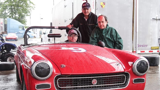 Mike Pinney sits in the 1966 MG Midget he won the 1978 SCCA Runoffs with alongside its current owners Craig (left) and Derek Chima.
